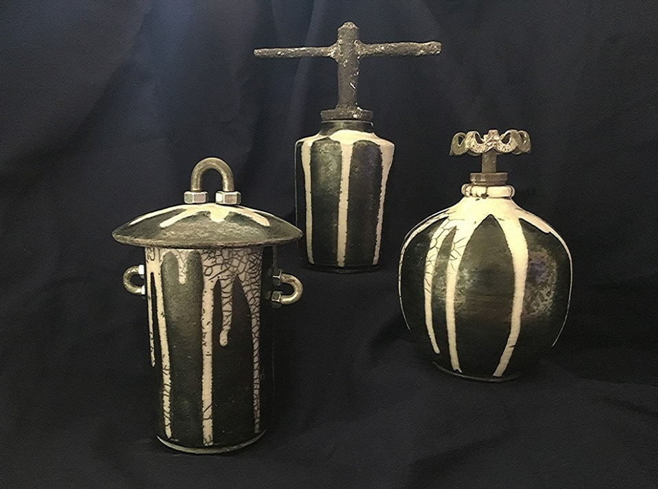 three black pots with dripped white glaze and hardware handles