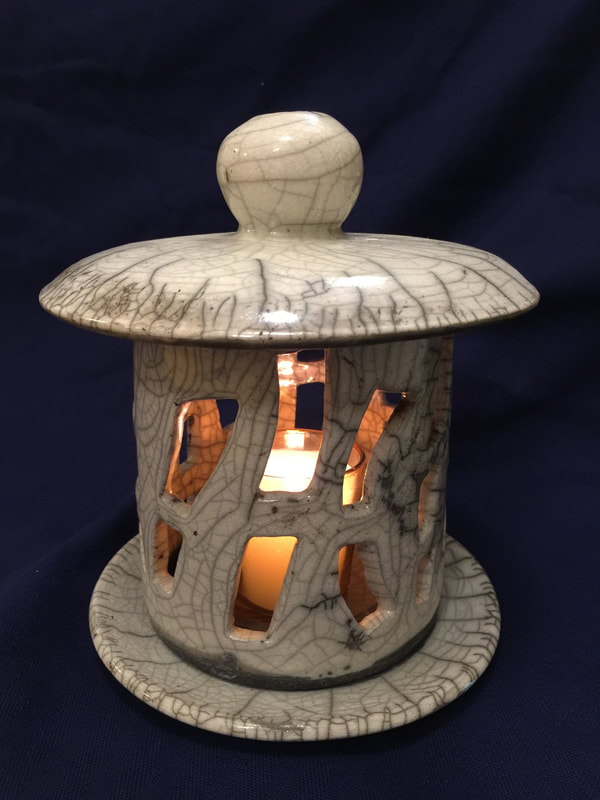 white raku fired candle lit lamp with lid