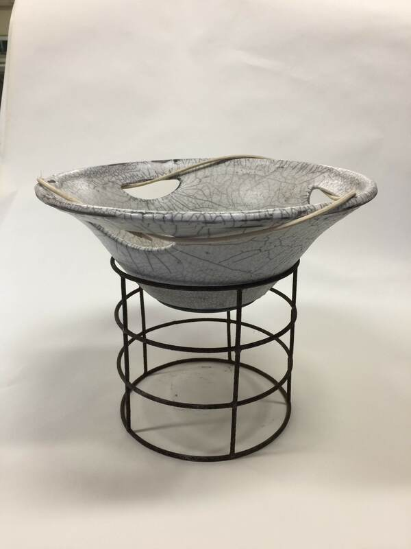 white raku fired bowl mounted on iron ring stand
